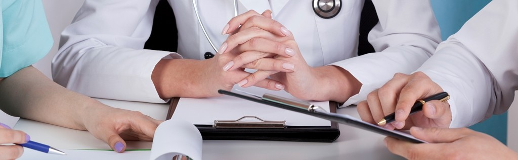 Close-up of hands of doctors with clipboards, horizontal